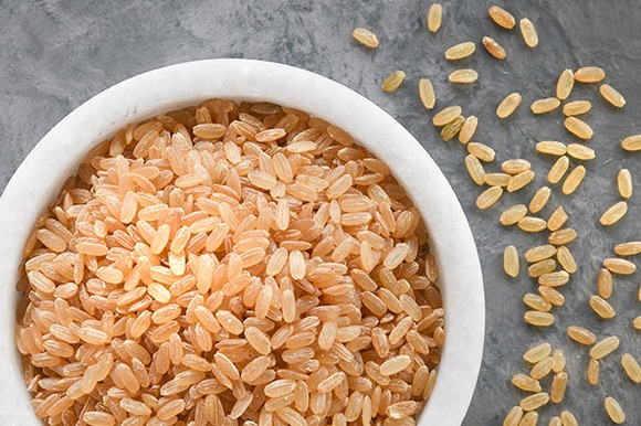 organic medium grain parboiled brown rice in bowl overhead